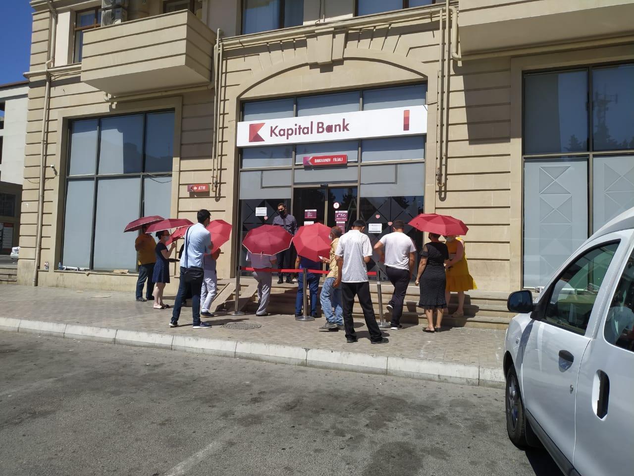 Kapital Bank filialların önündə müştəriləri günvurmadan qoruyur